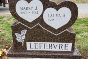 Double heart gravestone with calla lilies carved on Cat's Eye granite